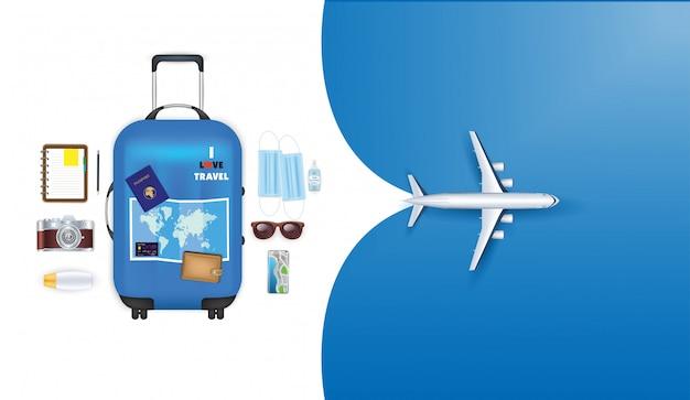 Viajar nuevo concepto de estilo de vida normal. máscaras maleta azul con gafas de sol, mapa, sombrero y cámara