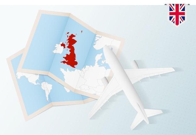 Viaje a reino unido, avión de vista superior con mapa y bandera de reino unido.
