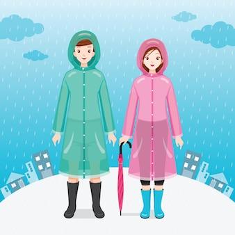 Viajero masculino y femenino vistiendo impermeables, de pie bajo la lluvia juntos