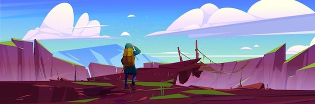 Viajero en viaje de puente viejo suspendido de montaña