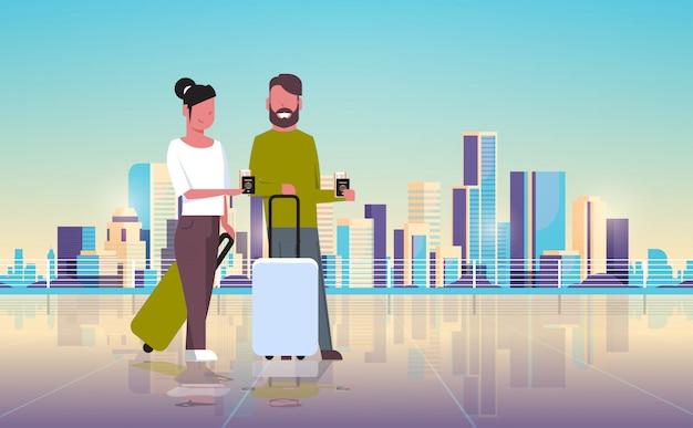 Viajeros con equipaje con pasaportes y boletos sobre el moderno edificio de la ciudad