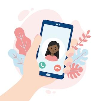 Videollamada entrante. mano sosteniendo un teléfono inteligente. linda chica haciendo una videollamada. personas que usan una aplicación de videollamadas mientras se distancian socialmente.