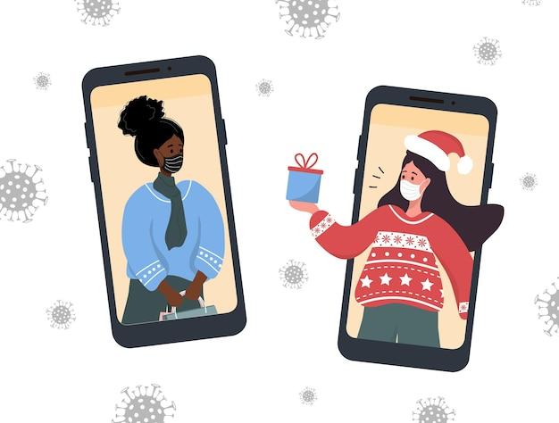 Videollamada de navidad. novias en mascarillas compartiendo regalos online.