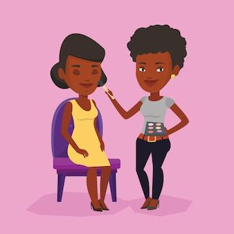 Visagiste haciendo maquillaje a niña.