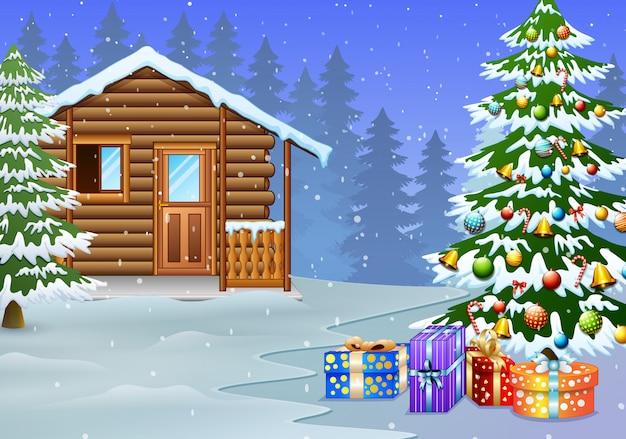 Vista de la casa de madera nevada y la decoración del árbol de navidad con el regalo.