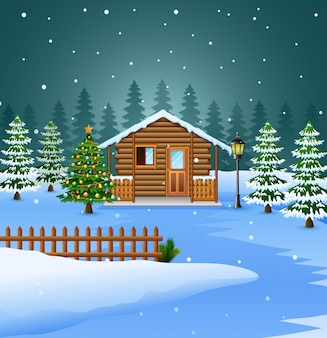 Vista de la casa de madera nevada y la decoración del árbol de navidad