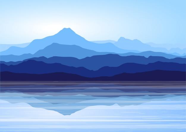 Vista de las montañas azules con reflejo en el lago