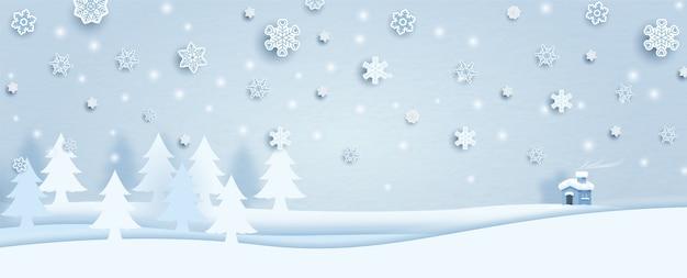 La vista del paisaje del bosque de pinos de invierno con copos de nieve y una casita sobre fondo azul hielo. todo en estilo de corte de papel y diseño de banner.