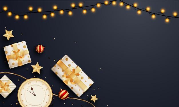 Vista superior de cajas de regalo con reloj de pared, estrellas doradas y guirnalda de iluminación decorada en negro con copyspace