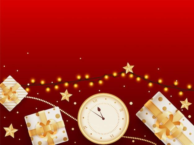 Vista superior de cajas de regalo con reloj de pared, estrellas doradas y guirnalda de iluminación decorada en rojo