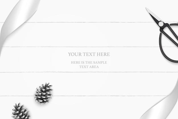 Vista superior elegante composición blanca cono de pino de cinta de plata y tijeras de metal vintage sobre fondo de piso de madera.