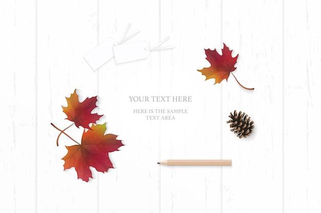 Vista superior elegante composición blanca papel rojo otoño hoja de arce cono de pino y etiqueta de lápiz sobre fondo de madera.