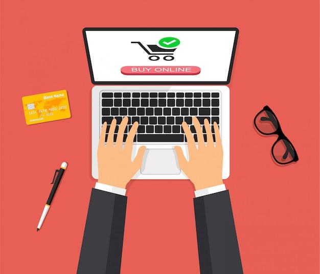 Vista superior del espacio de trabajo. carro de compras en la pantalla de un portátil. las manos están escribiendo en el teclado de la computadora y presionan un botón. las compras en línea. ilustración de vector de estilo 3d.