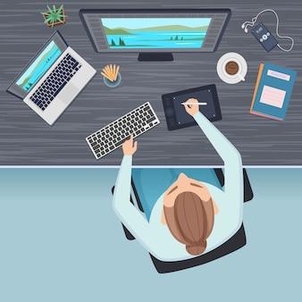 Vista superior del espacio de trabajo. mesa de oficina independiente y gerente o autónomo que trabaja en la computadora sentado en el escritorio