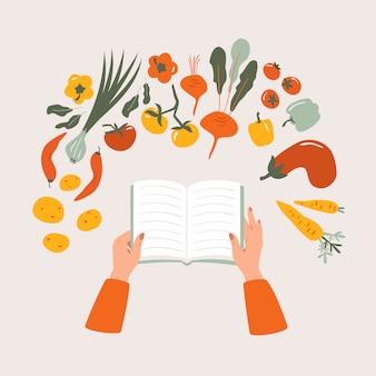 Vista superior del libro de cocina de dibujos animados en la mano sobre la mesa rodeada de varios vegetales.