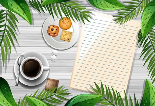 Vista superior de la mesa de madera con papel en blanco y una taza de café y elemento de hojas