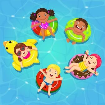 Vista superior de niños flotando en inflable en la piscina.