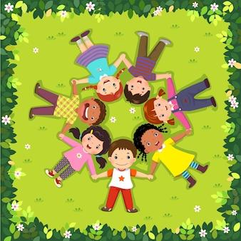 Vista superior de los niños tumbados en la hierba en un círculo