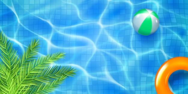 Vista superior de la piscina con mosaicos, anillo inflable, bola y hojas de palma. superficie del agua en colores azul claro con reflejos de luz solar y ondulaciones cáusticas. fondo de vacaciones de verano.