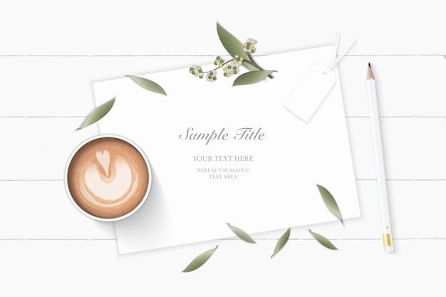 Vista superior plana endecha elegante papel blanco composición jardín botánico planta hoja flor pino cono etiqueta lápiz y café sobre fondo de madera.