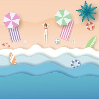Vista superior de playa y mar con mujer en conjunto de bikini y sombrillas en verano con corte de papel