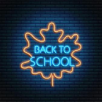 Volver a la escuela brillante cartel de neón con hoja de otoño.