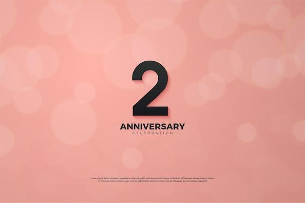 2. jahrestag mit schwarzer zahlenillustration auf rosa hintergrund mit bokeh-effekt.