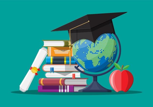 Abschlusskappe auf festgeklebten büchern mit globus und apfel