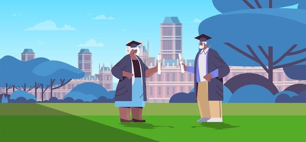 Absolventen des älteren mannes, die im park zusammenstehen, absolventen, die akademischen abschluss feiern