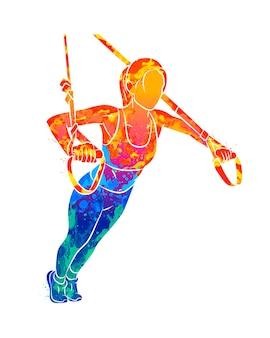 Abstrakte junge sportliche frau, die liegestütze unter verwendung von trx fitnessbändern vom spritzen von aquarellen tut. illustration von farben