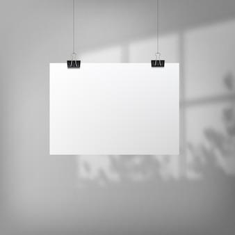 Abstraktes plakatdesign mit hängendem papier. hängendes papierplakatmodell. ein blatt papier hängt an einem wandhintergrund mit überlagerten schatten vom fenster und vegetation außerhalb des fensters