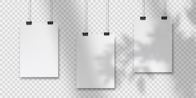 Abstraktes plakatdesign mit hängenden papieren. hängendes a4-postermodell. drei blätter papier hängen vor einem wandhintergrund mit überlagerten schatten vom fenster und vegetation außerhalb des fensters