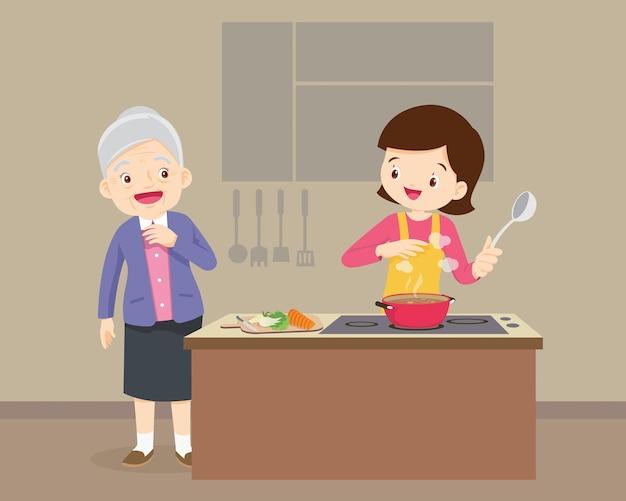 Ältere frau, die frau sieht, die in der küche kocht