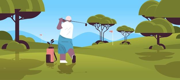 Ältere frau, die golf auf grünem golfplatz im alter von afroamerikanischem spieler spielt, der einen schuss aktives alterskonzept macht