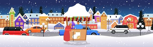 Ältere frau in der nähe von stall mit weiblichen verkäufer weihnachtsmarkt wintermesse konzept frohe weihnachten feiertage feier moderne stadt straße stadtbild in voller länge horizontale vektor-illustration