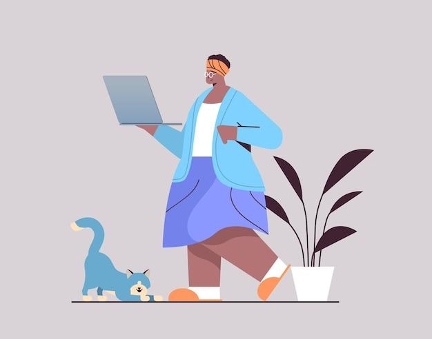 Ältere frau mit laptop-afroamerikaner-großmutter, die sich zu hause im social-media-netzwerk entspannt