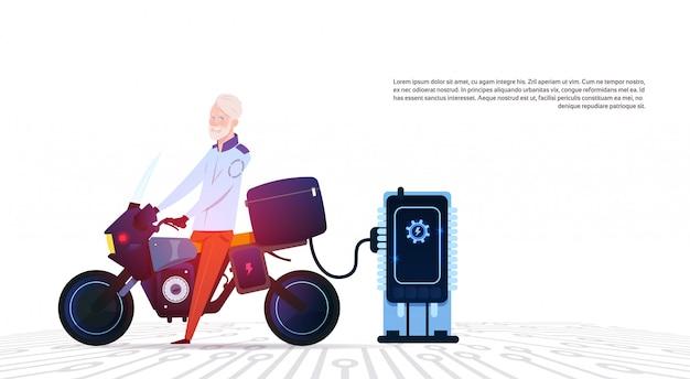 Älterer mann auf motorrad am elektrischen hybriden motorrad-konzept der elektrischen ladestation