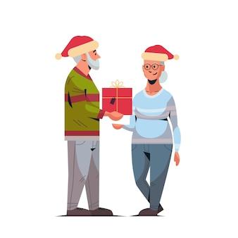 Älterer mann in der weihnachtsmütze, die geschenkgeschenkbox zur reifen frauenfamilie gibt, die frohe weihnachten frohes neues jahr winterferien-konzeptillustration feiert