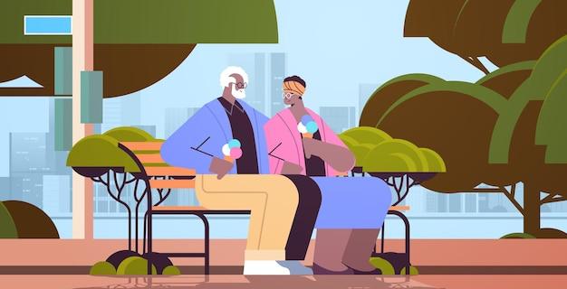 Älteres paar, das auf bank sitzt und eis isst, glückliche afroamerikanische großeltern, die zeit zusammen im park verbringen?
