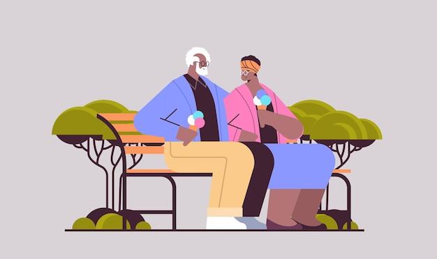 Älteres paar, das auf der bank sitzt und eis isst, glückliche afroamerikanische großeltern, die zeit zusammen im park verbringen, horizontale vektorillustration in voller länge