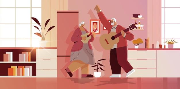 Älteres paar, das gitarre spielt, großeltern, die spaß haben, aktives alterskonzept, hauskücheninnenraum horizontal