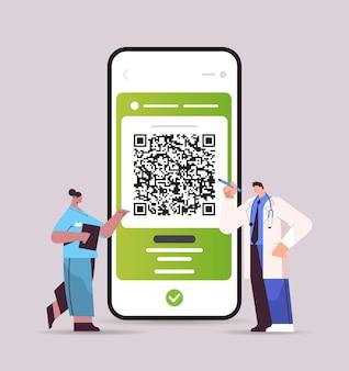 Ärzte, die einen digitalen immunitätspass mit qr-code auf dem smartphone-bildschirm verwenden, risikofreie covid-19-pandemie