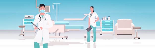Ärztepaar in uniform arbeiten zusammen im operationssaal moderne krankenhausklinik innen teamwork-konzept horizontal