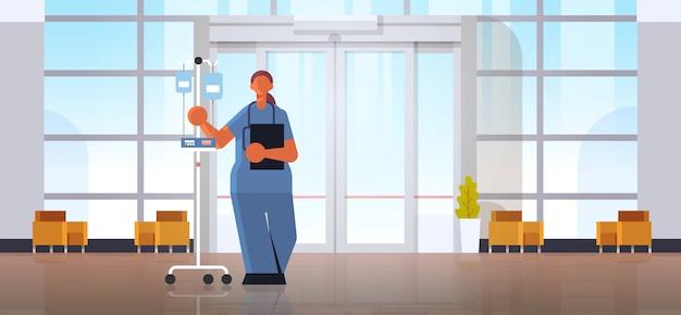 Ärztin anästhesistin in uniform holding dropper medizin gesundheitswesen konzept moderne krankenhausklinik halle innenraum in voller länge horizontal flach
