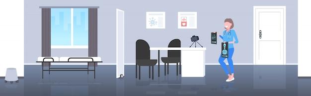 Ärztin blogger, der das röntgenbildchirurg-aufnahmevideo mit kamera auf blogging konzept der modernen klinik der stativmedizin in voller länge horizontal überprüft