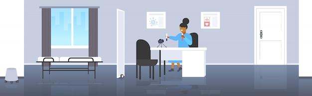 Ärztin blogger, der reagenzgläser mit unterschiedlichem flüssigem afroamerikanerfrauenwissenschaftler-aufnahmevideo mit kamera auf dem stativ bloggt die moderne horizontale klinik des konzeptinnenraums in voller länge hält