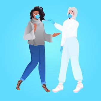 Ärztin in maske, die einen tupfertest für eine coronavirus-probe aus einer pcr-diagnose einer afroamerikanischen patientin durchführt