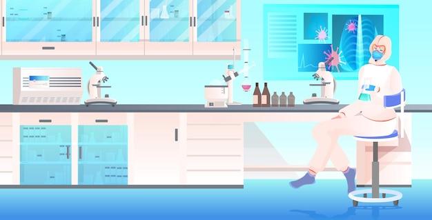 Ärztin in maske und schutzanzug arbeitet mit reagenzglas in der impfstoffentwicklung im medizinischen labor