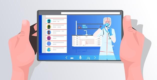 Ärztin in maske und schutzanzug, die mit reagenzglas auf tablettenbildschirm-impfstoffentwicklung arbeitet