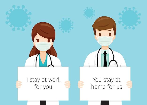 Ärztinnen und ärzte, die chirurgische masken tragen, banner halten, ich bleibe für sie bei der arbeit, sie bleiben für uns zu hause